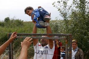 Syrische vluchtelingen tillen een kind over de prikkeldraad aan de grens met Hongarije. (foto Reuters)
