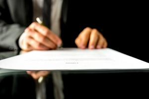 Close up low angle view of the blurred hands of a businessman signing a document or contract with focus to the text Contract. Shallow dof.