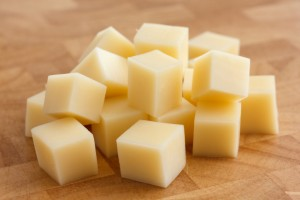 Cubes of yellow cheese stacked randomly on wood chopping board.