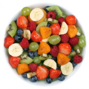 Fruit salad in a bowl with fruits like strawberries, kiwi, apricots and blueberries from above