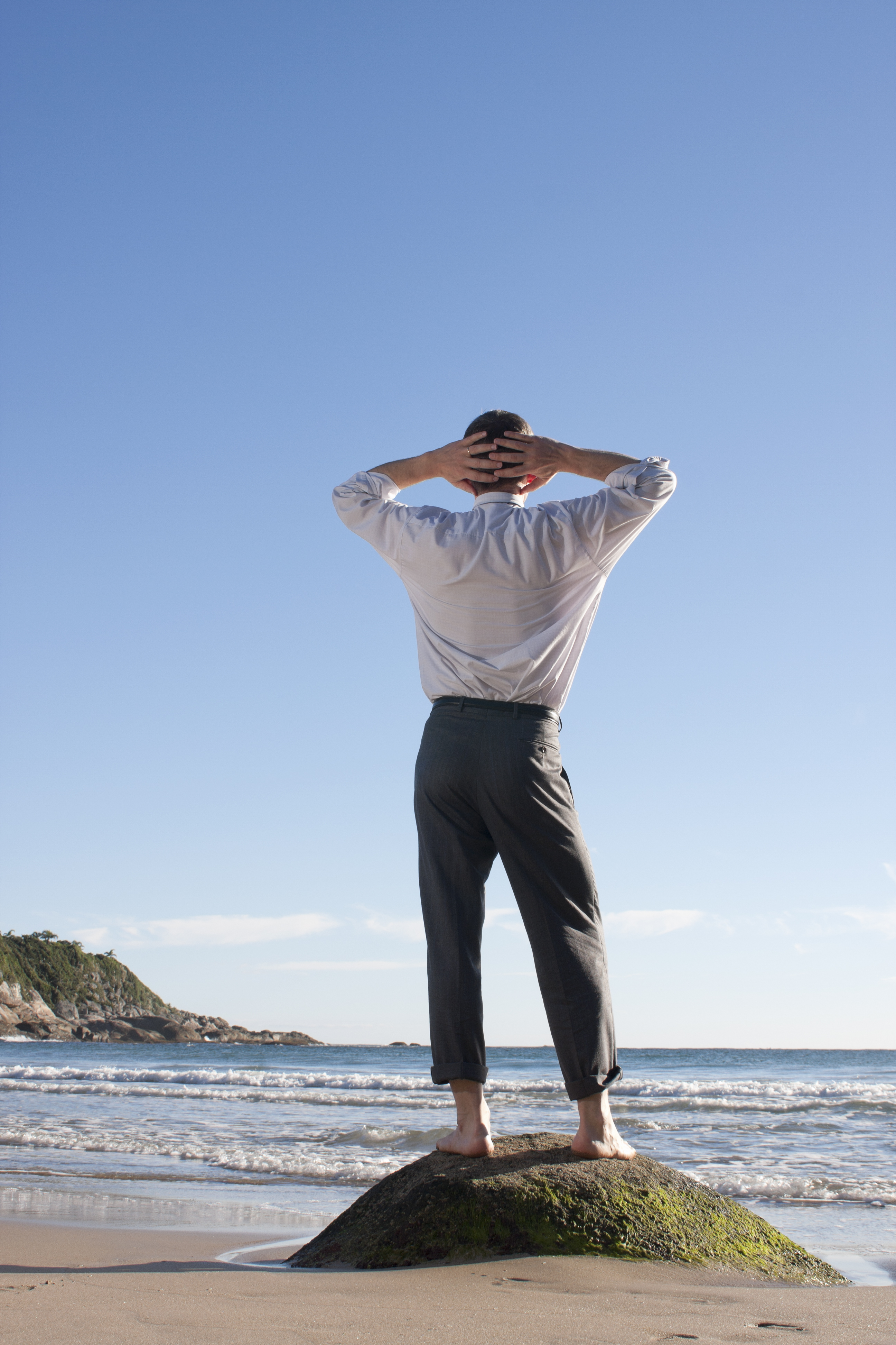 Businessman standing barefoot on a rock at the sea
