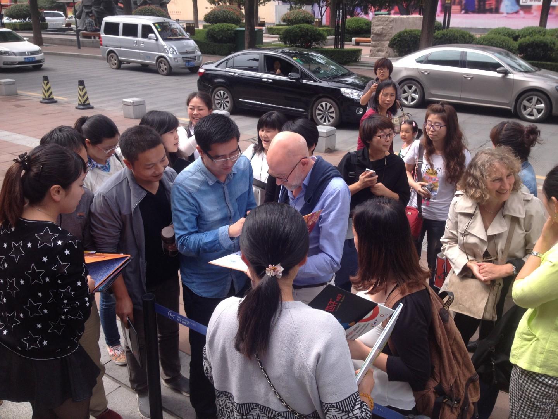 Guido Van Genechten in China, aangeklampt door een horde fans.
