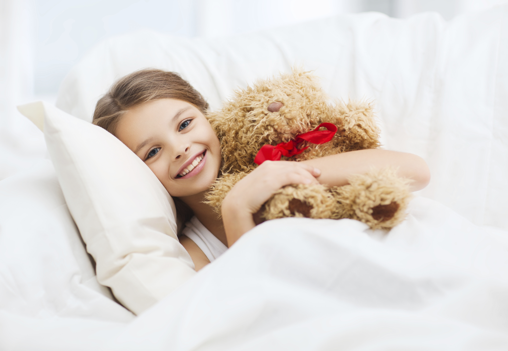 little girl with teddy bear sleeping in bed at home