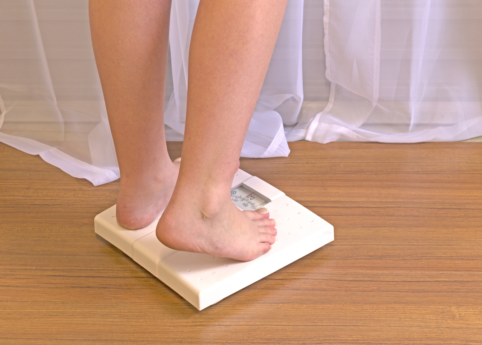 Young Energetic Girl Stepping on Bathroom Scale