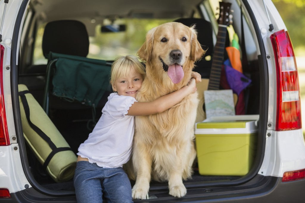 Smiling little girl with her dog in car trunk on a sunny day