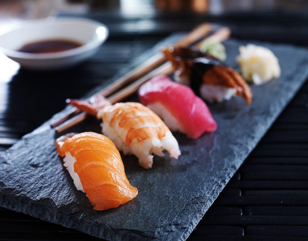 Close-up or assorted sushi nigiri on black slate