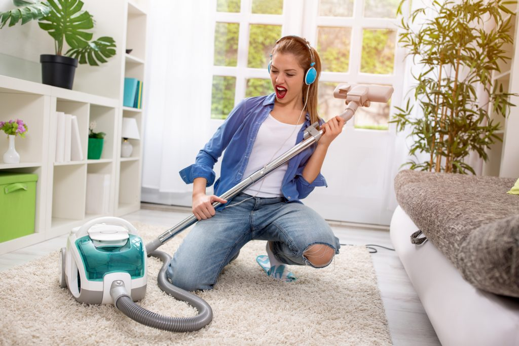 Smiling excited young housewife havig fun with vacuum cleaner