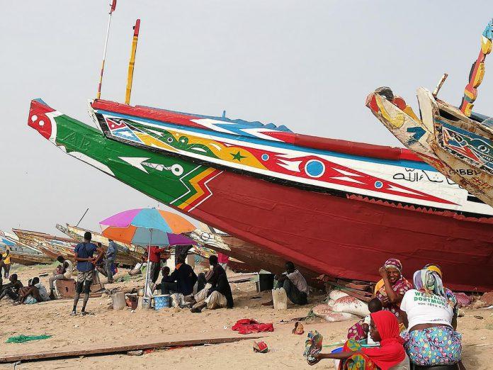 De gezellige drukte in Tanji, wanneer de kleurrijke vissersboten opnieuw op het strand liggen en kopers van boot tot boot trekken om verse vis op de kop te tikken.